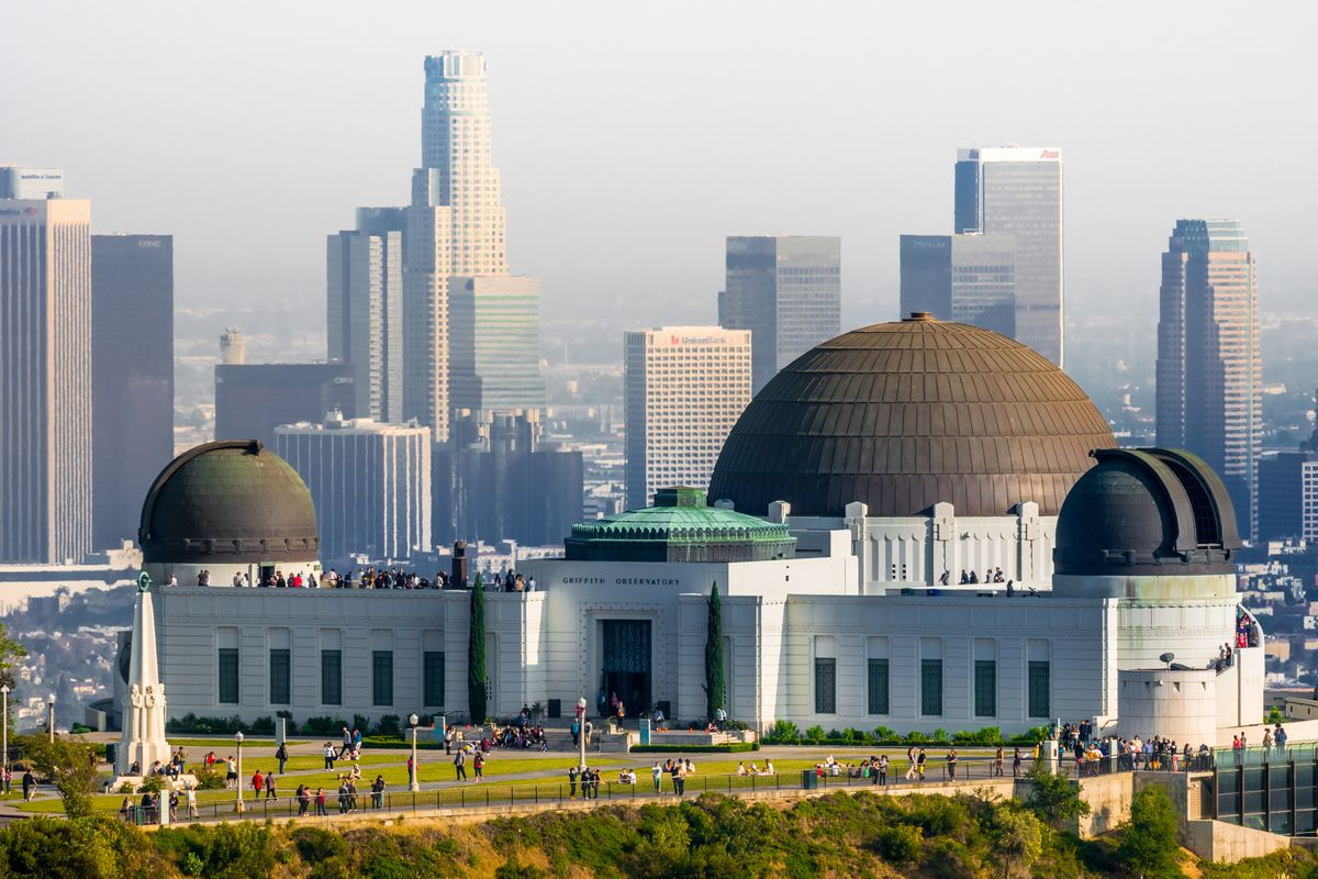 The exterior of the Griffith Park Observatory in Los Angeles. The building facade is white and there are multiple dome shaped structures on the roof. In the background is the city skyline of Los Angeles.