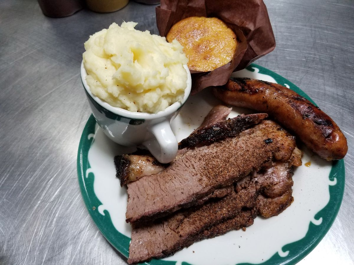 A plate of brisket, hot links, and sides.