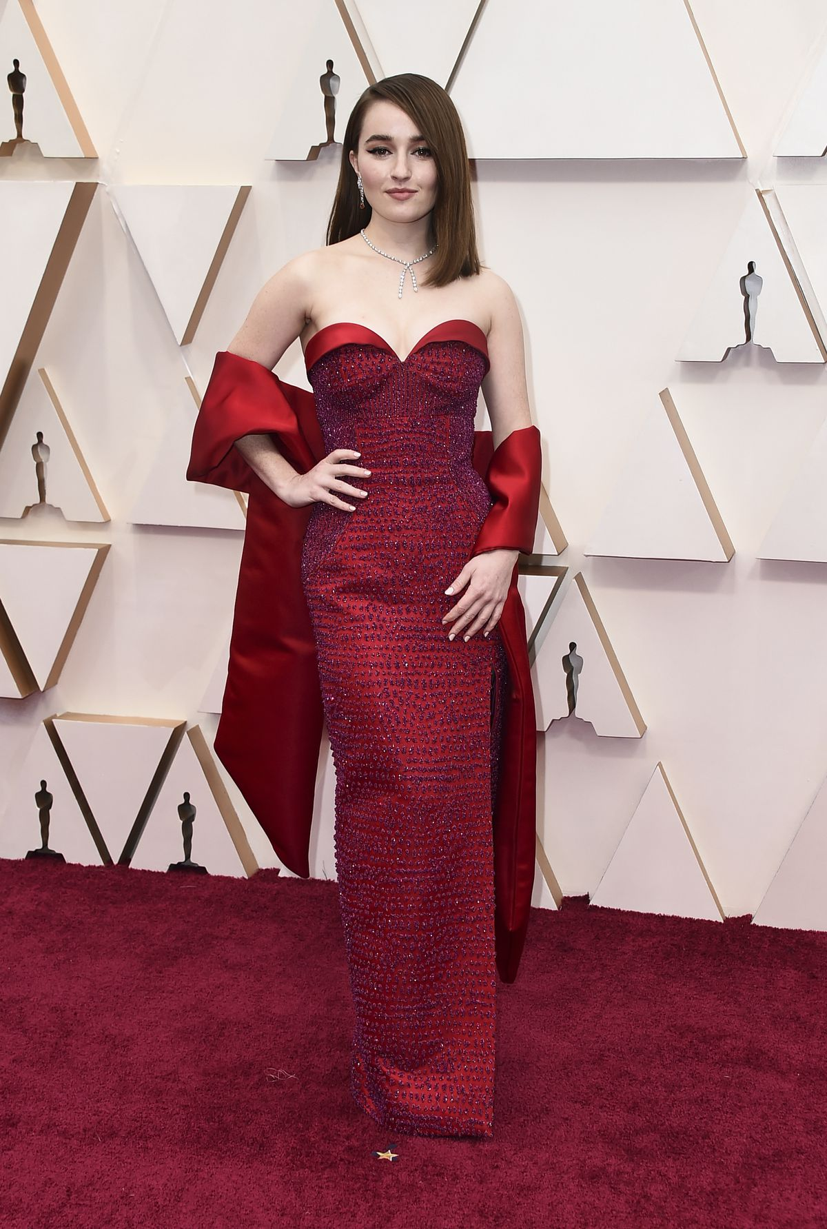 Kaitlyn Dever arrives at the Oscars wearing a scarlet Louis Vuitton couture gown designed with fuchsia glass beads and more than 14,000 Swarovski crystals.