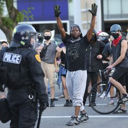 A protester decrying the police shooting of Bernardo Palacios-Carbajal raises his hands to police in Salt Lake City on Thursday, July 9, 2020.