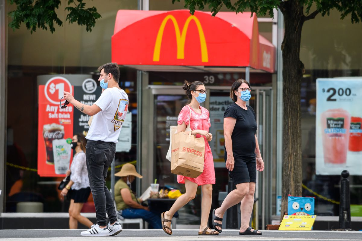 People wear protective face masks outside McDonald's in Union Square as New York City continued Phase 4 of reopening last year.