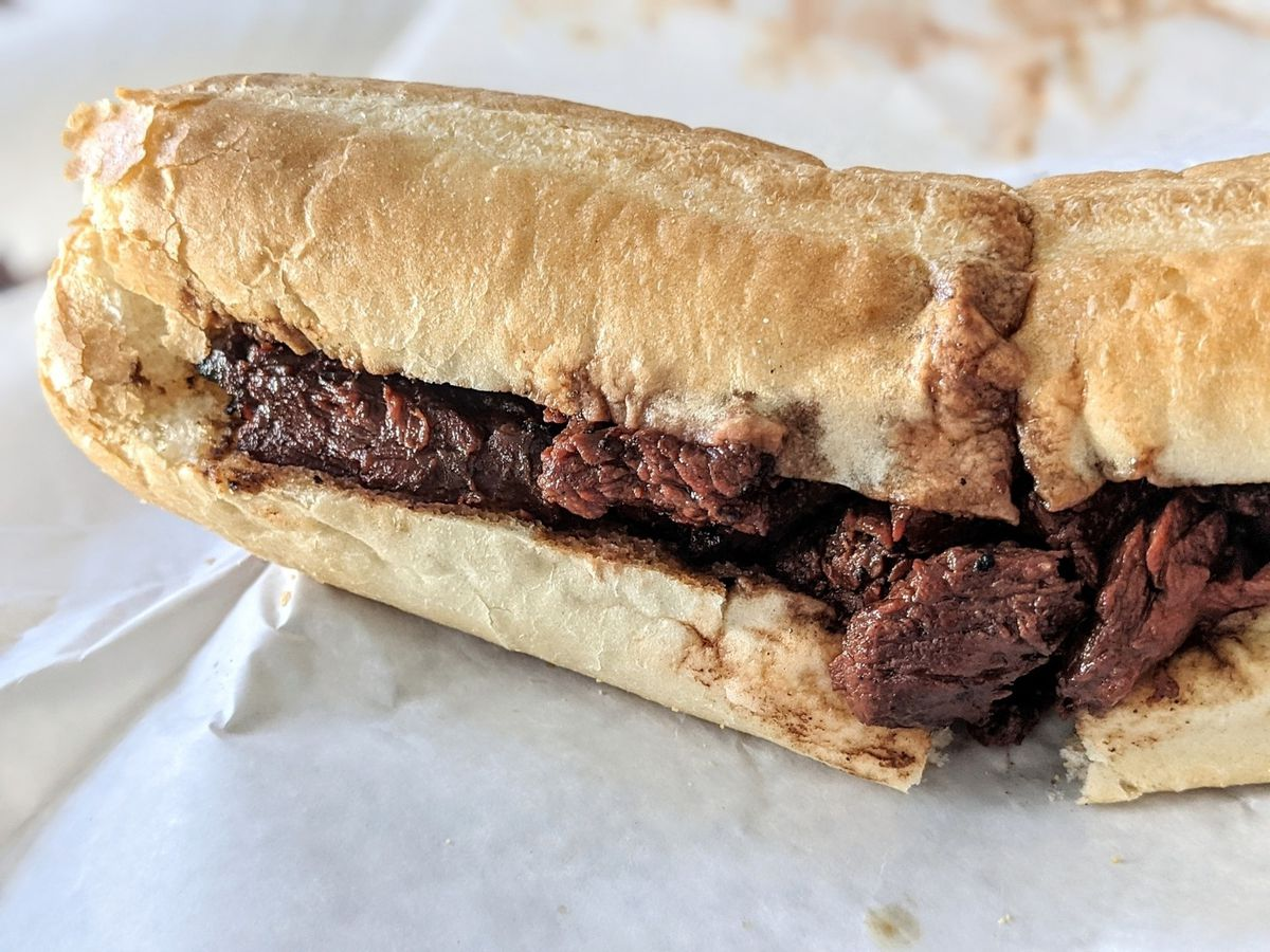 Closeup on a sub, split in half, filled simply with steak tips. It sits on a white paper.