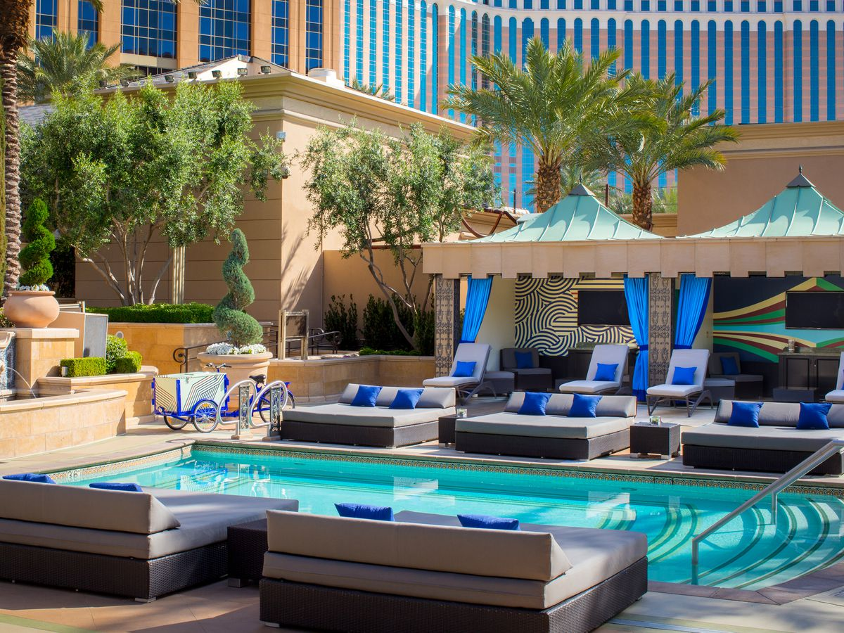 Small pool surrounded by cabanas with blue decor