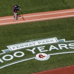 A member of the Fenway Park grounds crew prepares the first base line before a baseball game between the Boston Red Sox and the Tampa Bay Rays in  Boston, Friday, April 13, 2012. The Red Sox will celebrate the 100th anniversary of Fenway's opening when they host the New York Yankees next Friday.