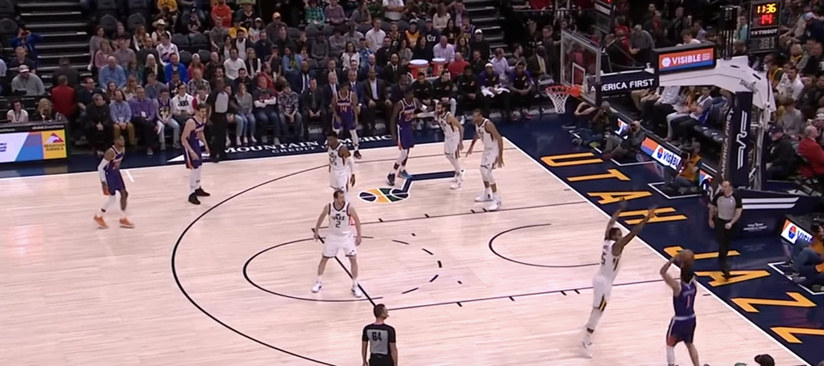 Devin Booker steps back for a 3, guarded by Derrick Favors