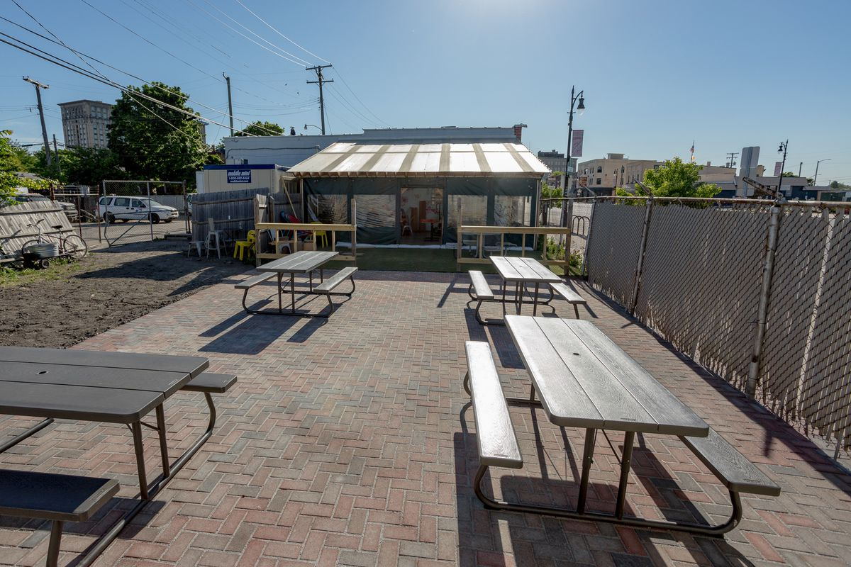 Picnic tables spread over a brick patio next to Ima's enclosed outdoor seating area.
