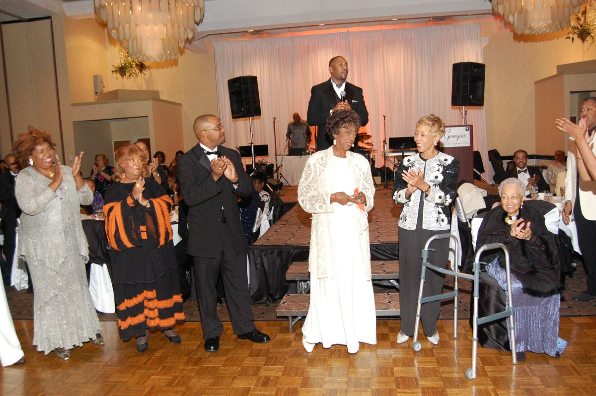 Rev. Henrietta Byrd (from left), Rev. Marjorie Cook, and Rev. Gaylon McDowell join Rev. Carry, Rev. Evelyn Boyd and Rev. Jeanette Childressat a banquet. Rev. Derrick B. Wells is standing at the podium.