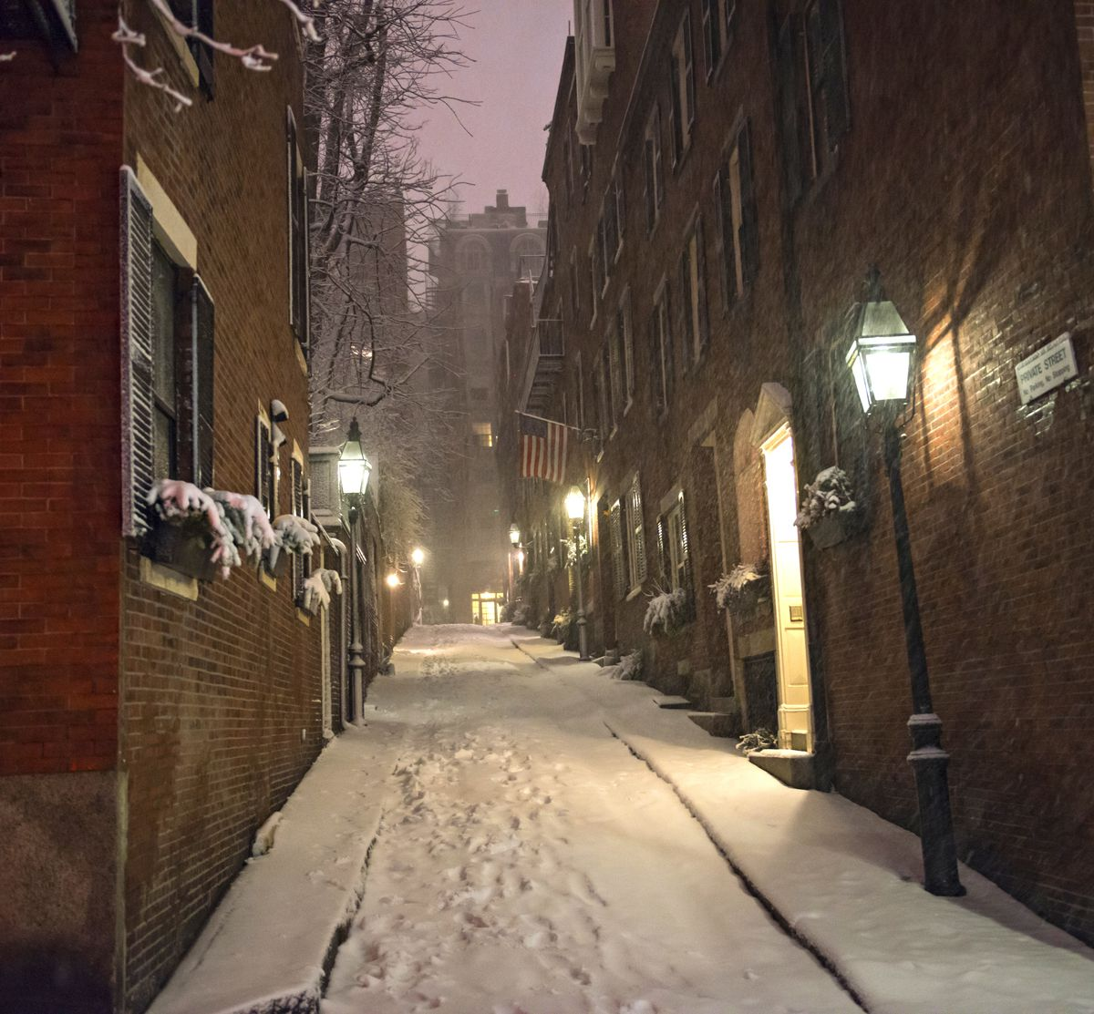 A narrow city street at nighttime with townhouses on either side, and there's snow on the ground.