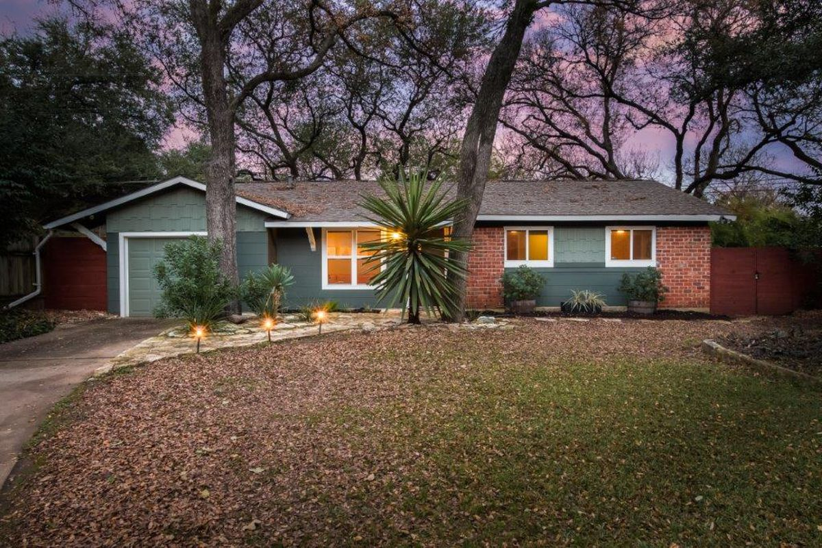 Classic one-story ranch-style 1961 home with alternating red-brick and light forest green wood facade, trees, front yard