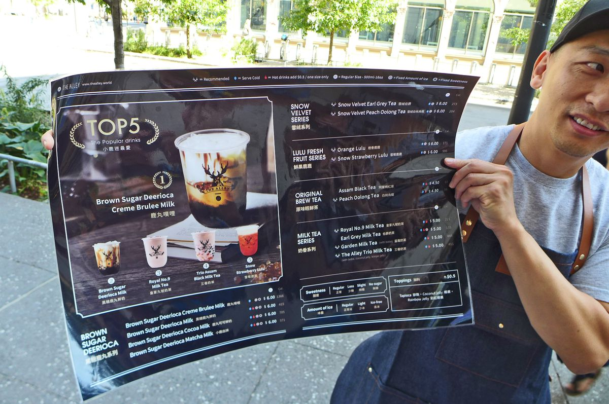 A man in a baseball cap stands outside holding a copy of the menu...