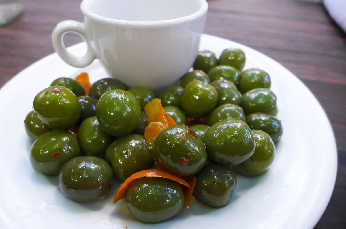 A plate of deep green olives with an expresso cup for pits.