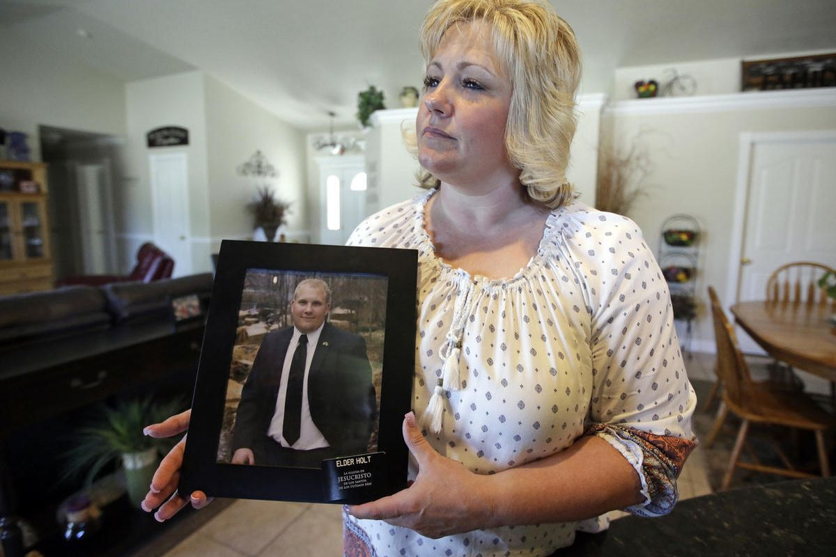 FILE - This July 13, 2016, file photo, Laurie Holt holds a photograph of her son Josh Holt at her home in Riverton, Utah. Venezuela prison guards forced Holt to strip naked in a hallway and perform exercises, his lawyer said Tuesday.
