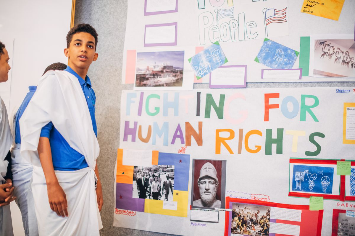 """Two students stand by a poster hanging on a classroom wall. The poster reads, """"fighting for human rights"""""""