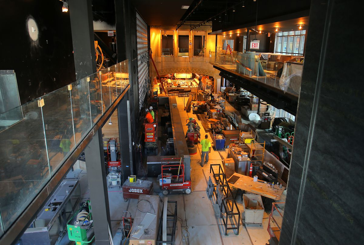 Ceiling view of workers renovating a high-ceilinged bar and grill.
