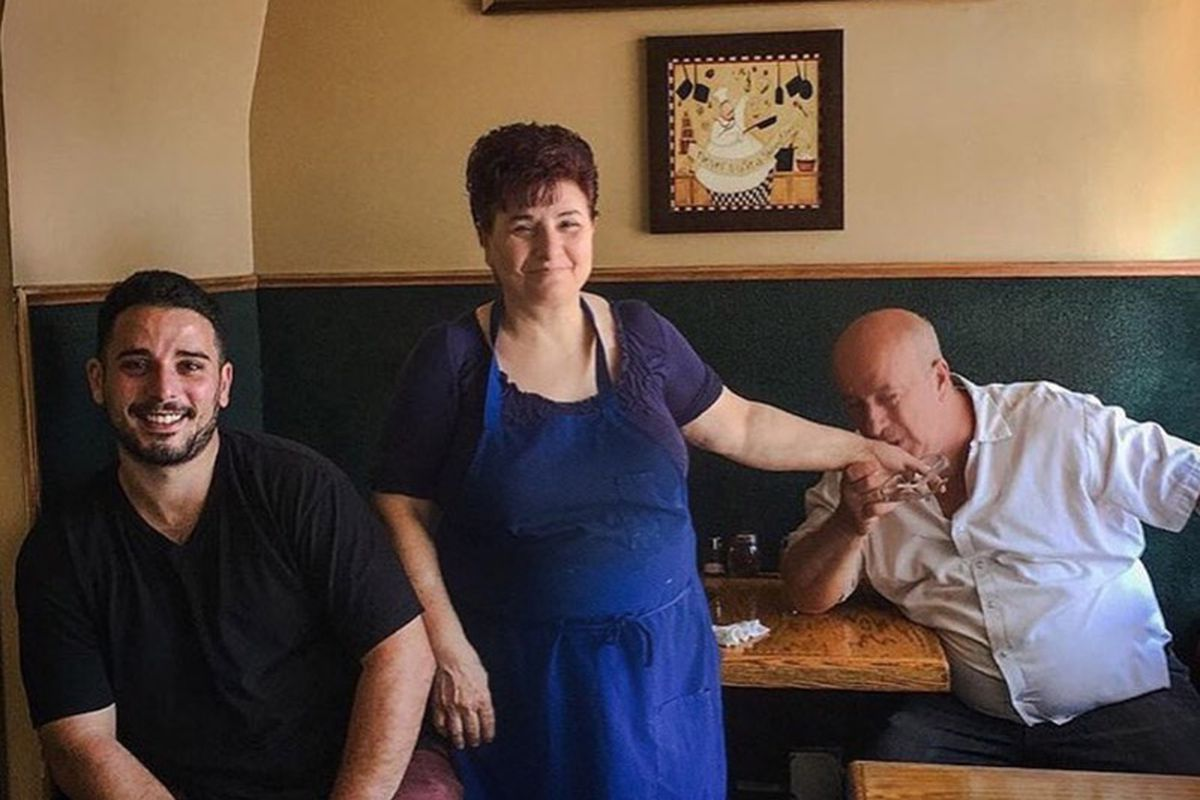 A three-person family sits inside their small, warm restaurant.