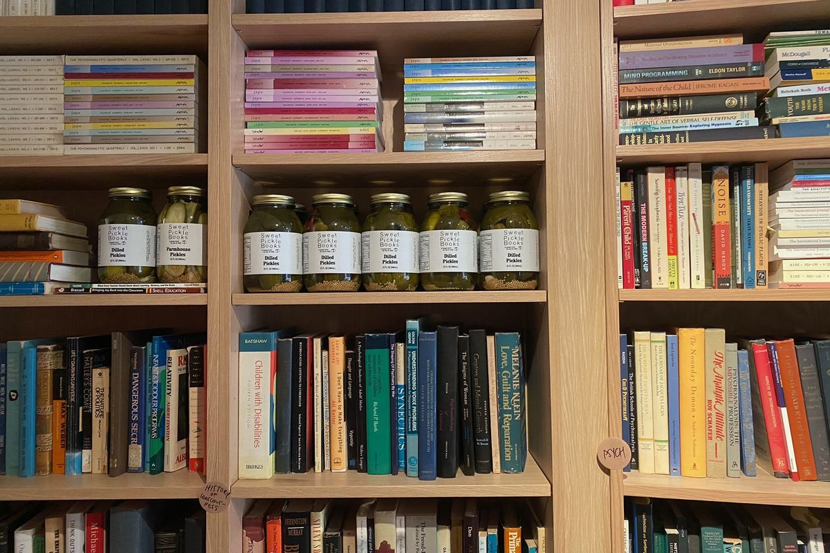 A photo of several bookshelves stacked with books and a line of pickle jars in the middle