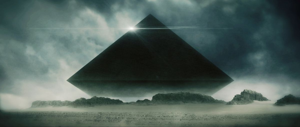a black pyramid floats over some sand