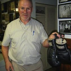 Larry Fullmer holds the boxing gloves that his father, Don Fullmer, used in his pivotal bout against Nino Benvenuti in 1968 for a world middleweight title.