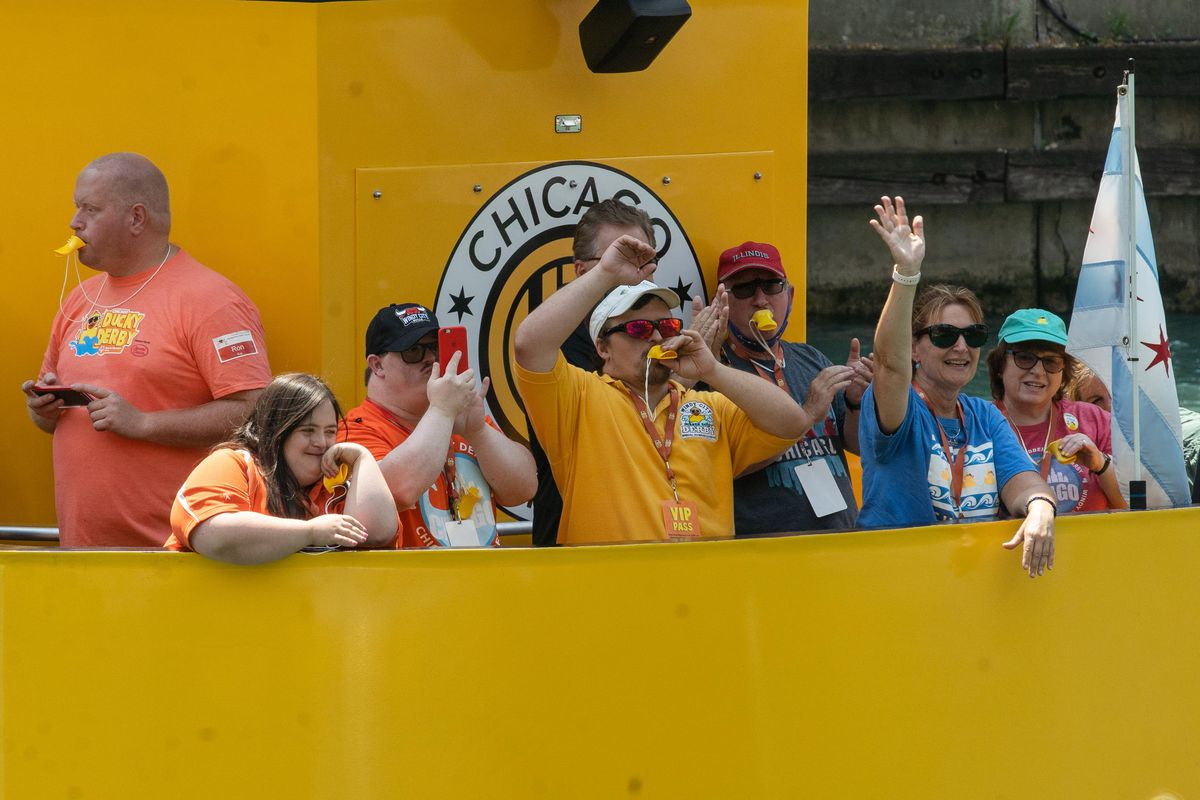 People on a water taxi wave before 70,000 rubber ducks were thrown into the Chicago River near the Columbus Bridge in the Loop during the Chicago Ducky Derby to raise funds for Special Olympics Illinois, Thursday afternoon, Aug. 5, 2021.