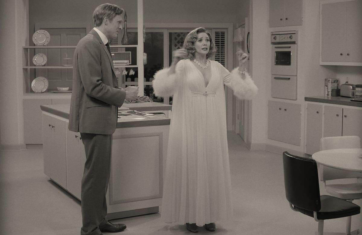 Wanda, in a white peignoir, stands in the kitchen with Vision in WandaVision