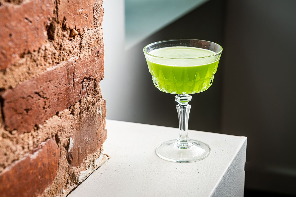 A bright green Hari Daiquiri in a coupe glass at Daru