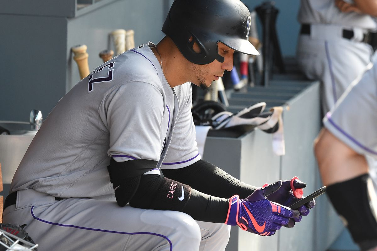A baseball player sits in the dugout wearing his uniform, batting helmet and batting gloves while checking his mobile phone.