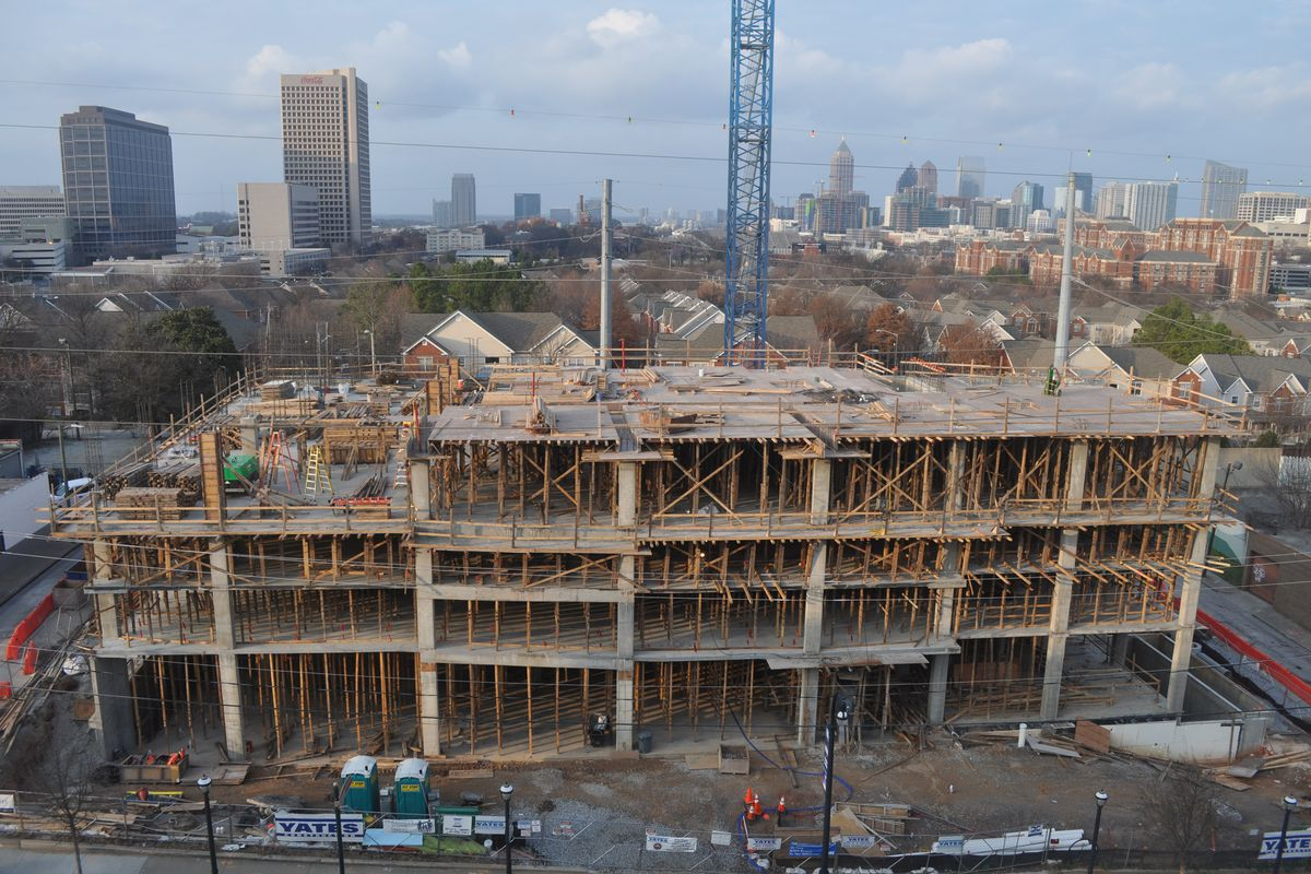 Construction underway, with four floors of concrete poured and the Atlanta skyline in the background.