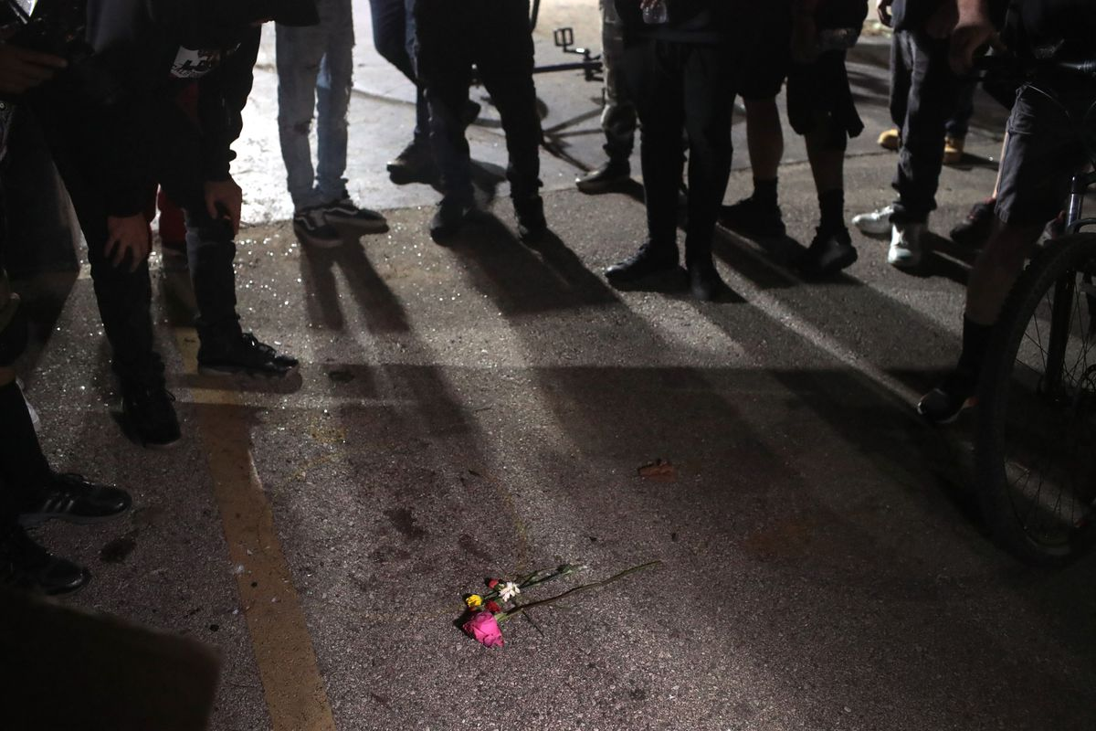 Demonstrators gather around a small memorial at the site where a young activist was shot and killed by a 17-year-old vigilante while protesting the shooting of Jacob Blake in Kenosha, Wisconsin. A Kenosha police officer shot Jacob Blake seven times in the back in front of his three children.