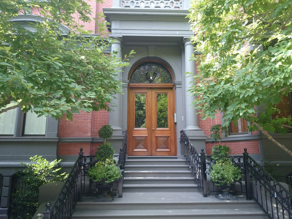 The front door of a small luxury building at the top of some steps.