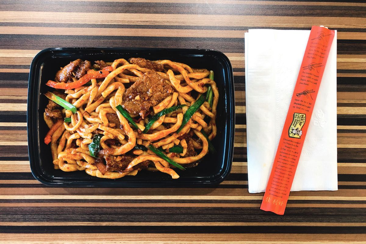 A takeout container of dry-fried noodles with beef at Silk Road Express in Allston, served on a striped wooden table with a pair of chopsticks
