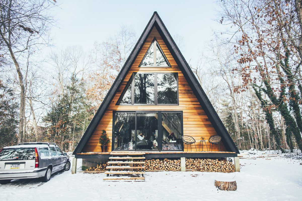 An A-Frame in Dorchester. This cabin is in New Jersey and is surrounded by trees. There is snow on the ground. There are logs under the frame of the house.