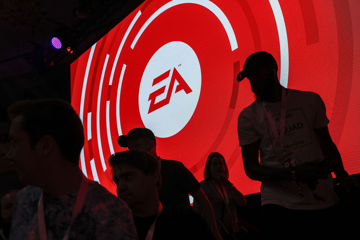 The silhouettes of attendees are seen standing in front of an Electronic Arts Inc. (EA) logo