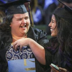 Salt Lake Community College graduates laugh with one another during the 2017 commencement ceremony at the Maverik Center in West Valley City on Friday, May 5, 2017.