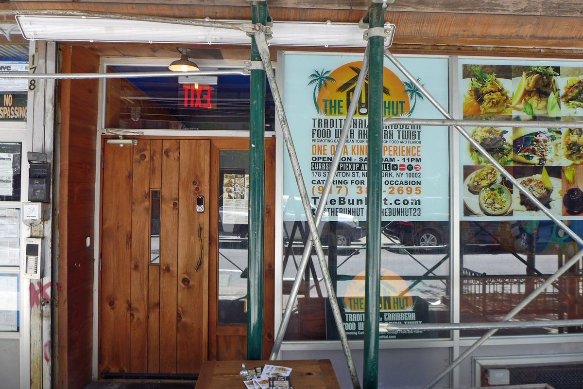 A storefront with metal scaffolds on the sidewalk in front.