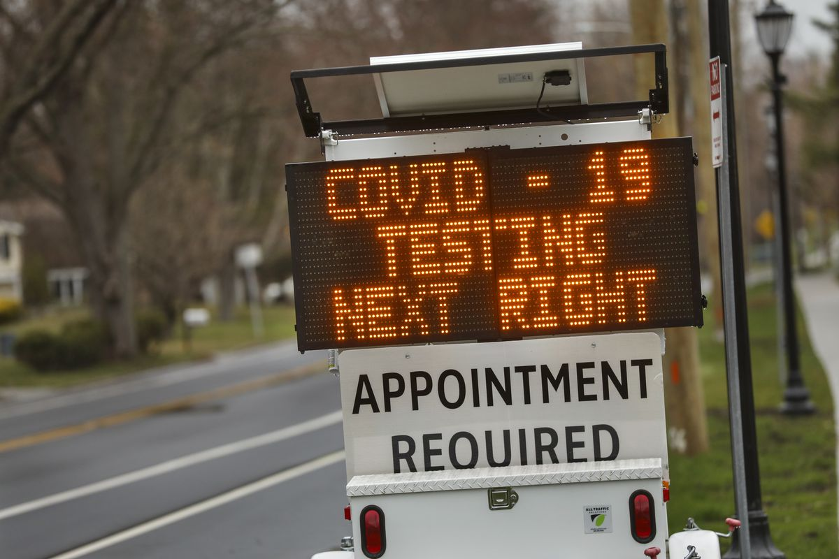 "A digital sign on a street reads, ""Covid-19 testing next right. Appointment required."""