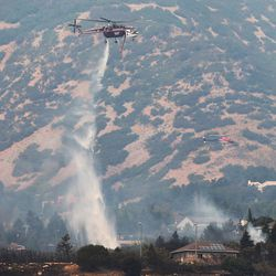 A air crane helicopter drops water on hot spots after a fire burned homes and property near Weber Canyon on Tuesday, Sept. 5, 2017.