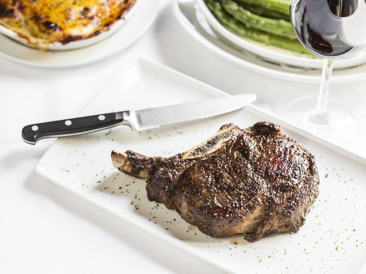 Bone-in steak served on a white plate with steak knife and side dishes in the background