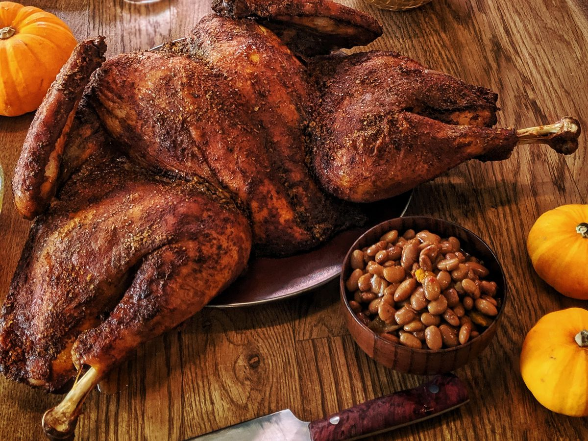 A seasoned, spatchcocked turkey  with a side of beans, and yellow pumpkins on a wooden counter