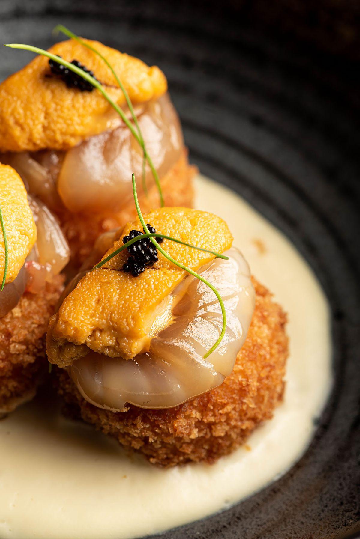 Closeup of truffle potato dish with uni, shrimp, and caviar.