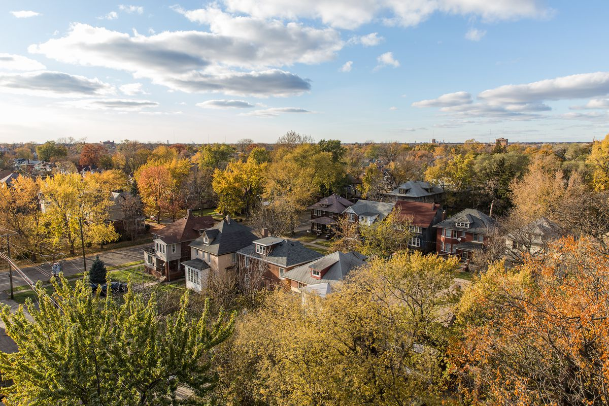 Aerial view of two streets lined with homes. There's colorful fall foliage on the many trees surrounding the homes.