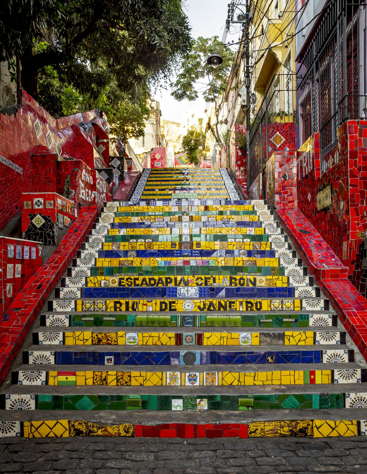 A stairway in Rio de Janeiro in Brazil. The stairway has colorful mosaic tiles that spell out different words. The sides of the staircase are covered with a red pattern. There is a tree at the top of the staircase.