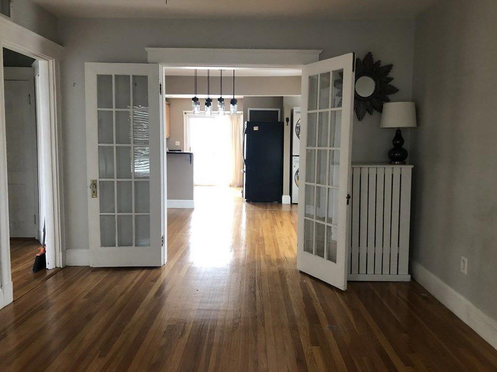 An open living room-dining room area separated by French doors, and the doors are open.