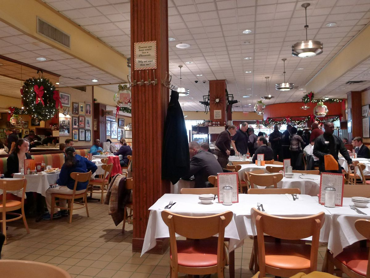 Groups of people sit at tables and waiters take their order in a busy diner