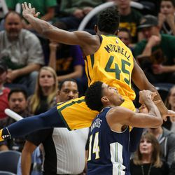 Utah Jazz guard Donovan Mitchell (45) is charged with a foul as he falls on Denver Nuggets guard Gary Harris (14) at Vivint Smart Home Arena in Salt Lake City on Tuesday, Nov. 28, 2017.