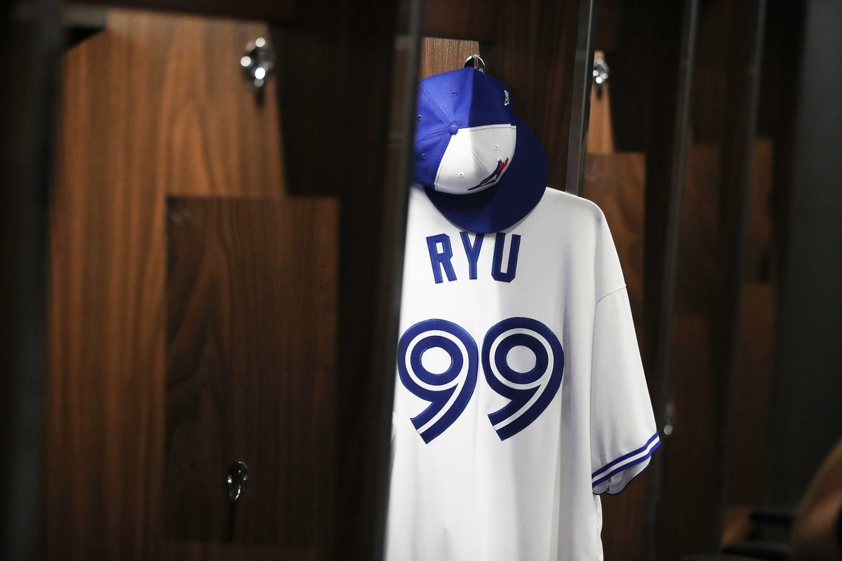 Hyun-Jin Ryu's #99 white Blue Jays jersey hanging in the clubhouse.