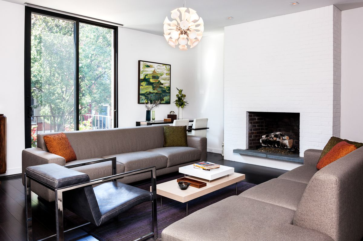Sleek, taupe-colored sofas flank a white fireplace with a metal hearth.