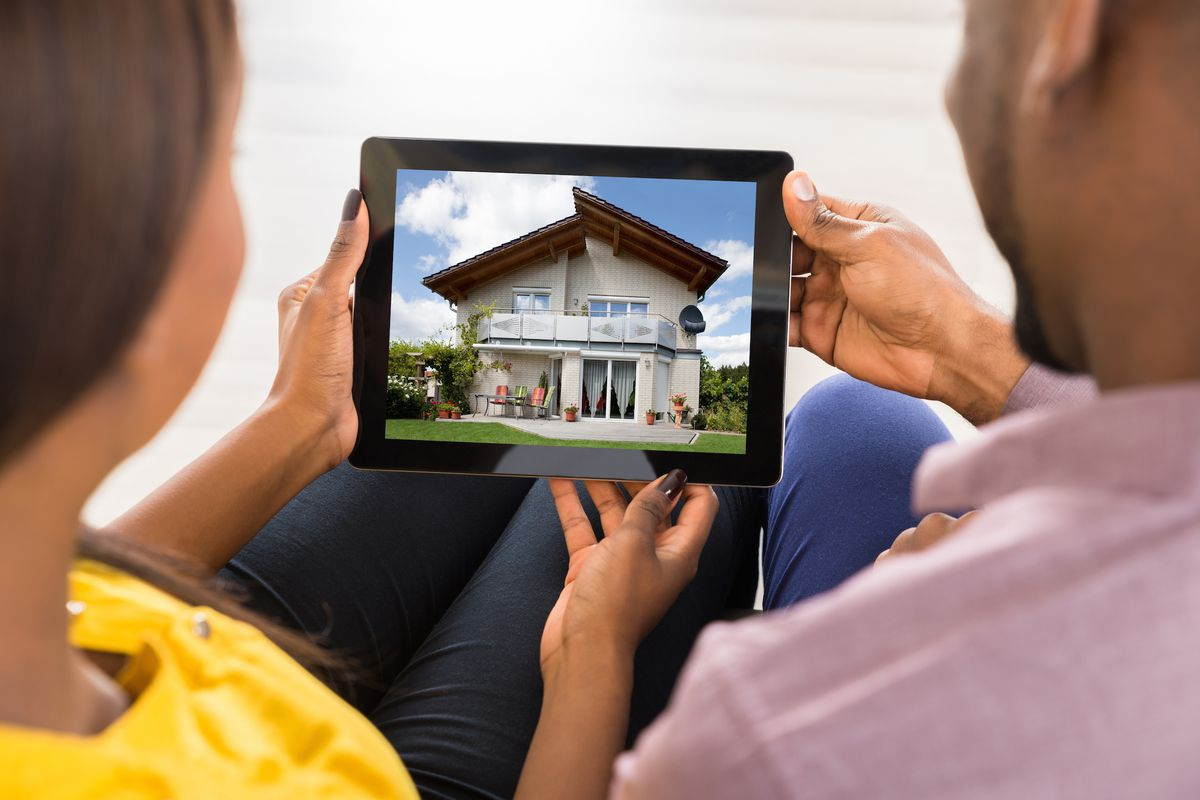 Couple looks at a house on a tablet
