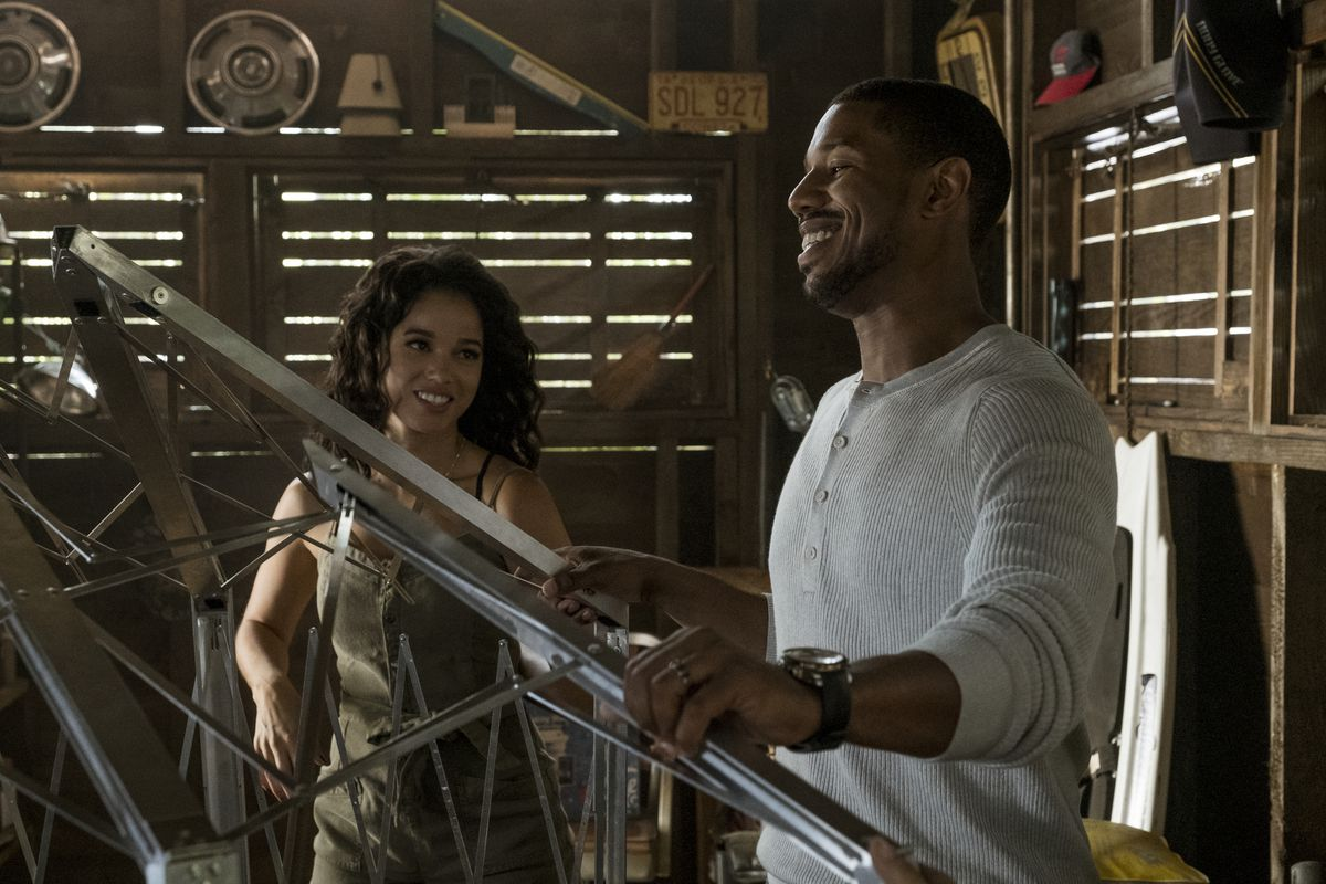 a man in a white shirt confidently works with some metal contraption, a woman smiles at him