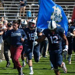 The UConn football team takes the field before their game with Virginia.