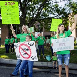 Lee Petersen with her son Brouan Lutes and Carlee Spencer join with other protesters demonstrating Friday, Aug. 8, 2014, prior to the Utah Board of Education's vote on whether to request an extended waiver from the Adequate Yearly Progress requirements of No Child Left Behind.